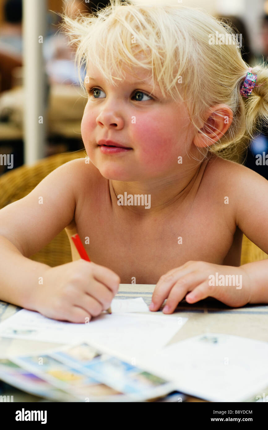 A little Scandinavian girl writing postcards. - Stock Image