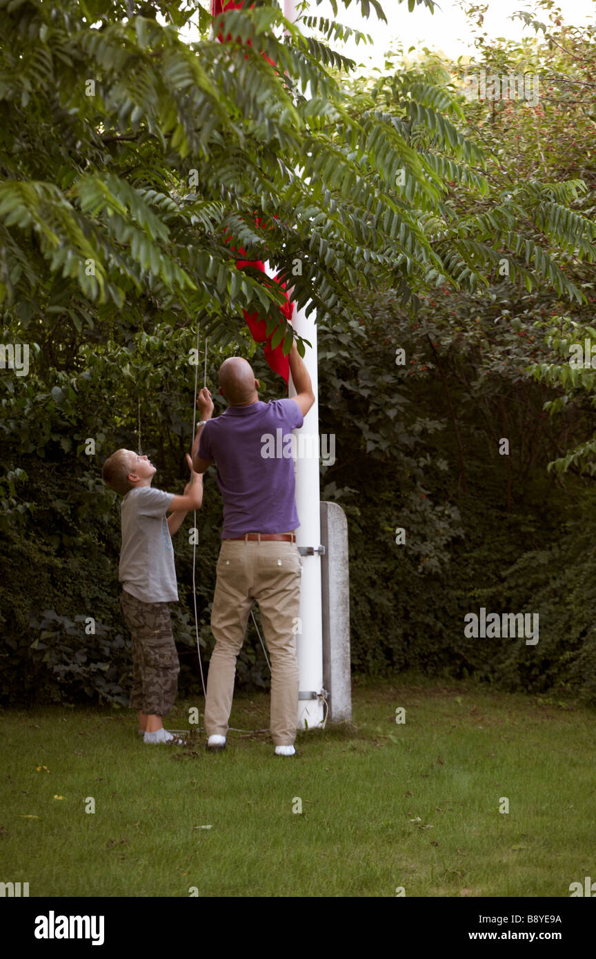 A man and a boy hoisting the Danish flag Copenhagen Denmark. - Stock Image