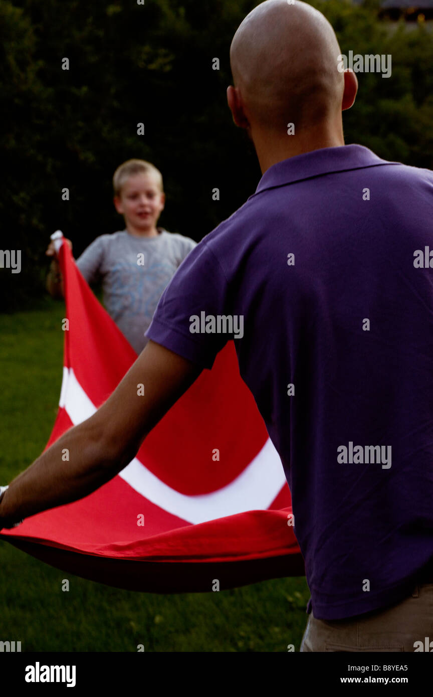 A man and a boy folding the Danish flag Copenhagen Denmark. - Stock Image