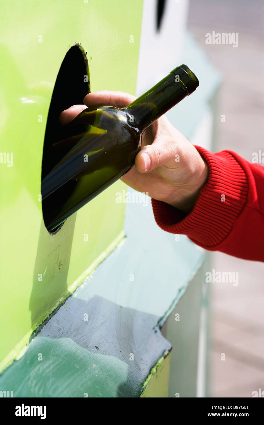 Recycling a bottle of glass close-up. - Stock Image