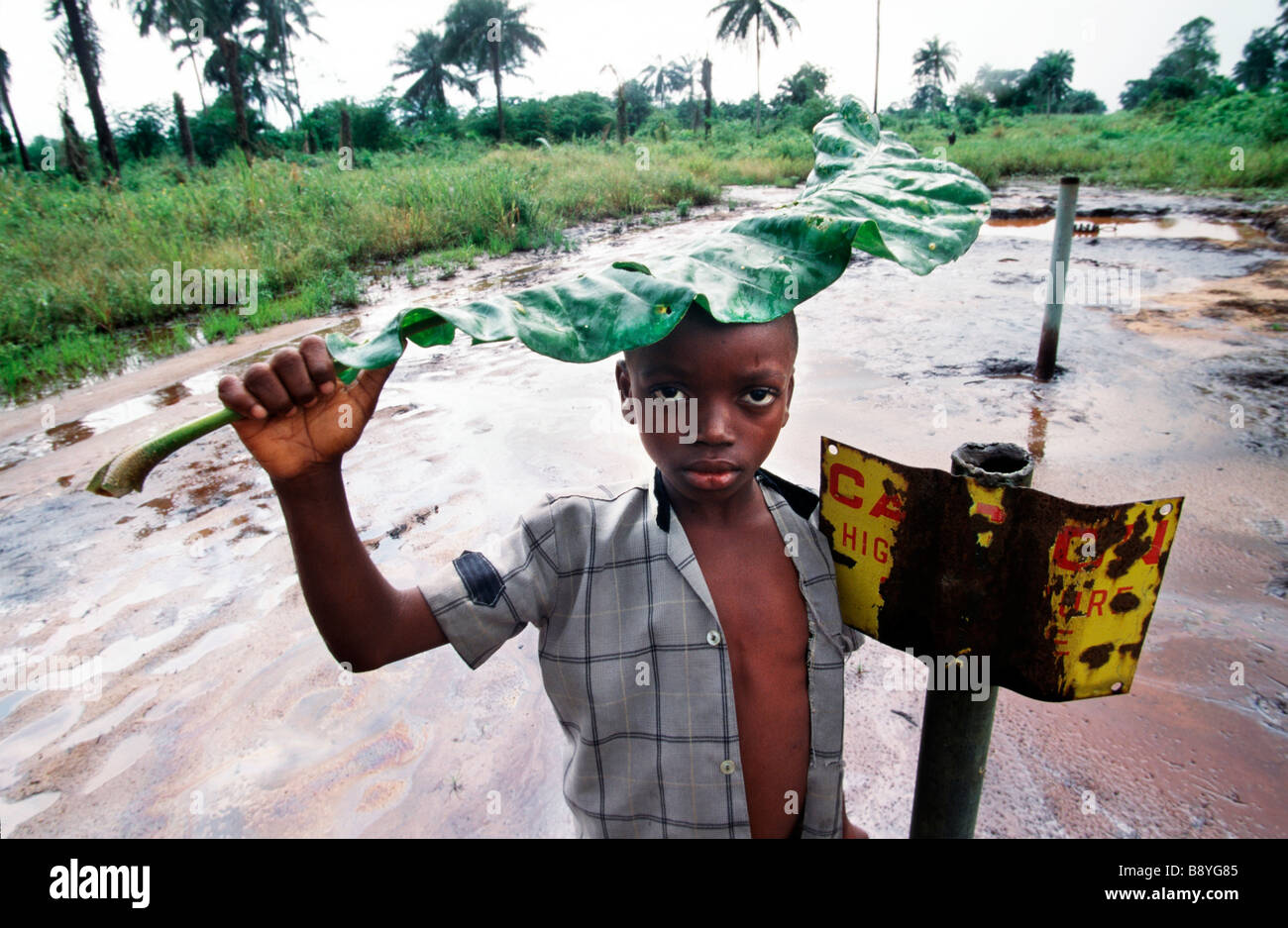 Nigeria: A boy stands besides a danger sign by an oil contaminated area in Ogoniland - Stock Image