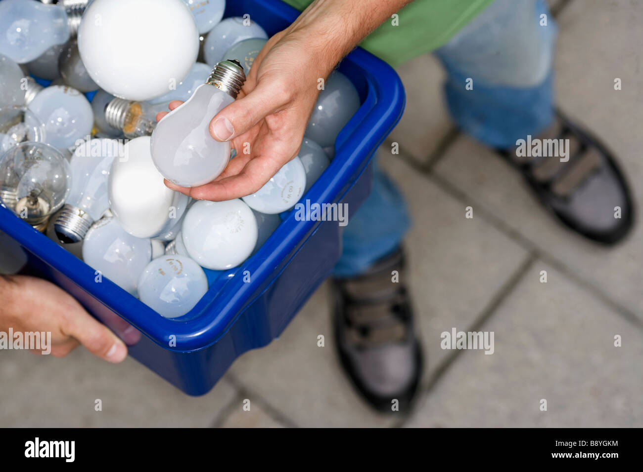 A man holding light bulbs for recycling. - Stock Image