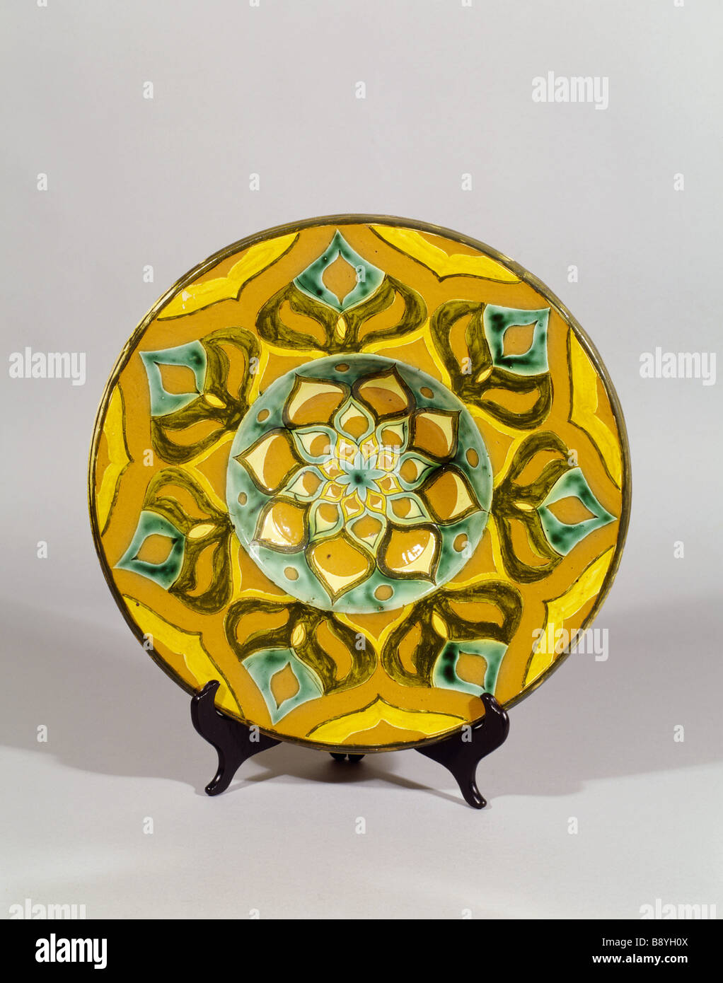 Della Robbia charger in the Morning Room at Standen a piece of ceramic with stylised flower pattern in yellow green - Stock Image
