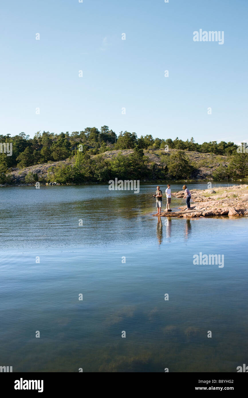Three boys fishing in the archipelago Sweden. - Stock Image