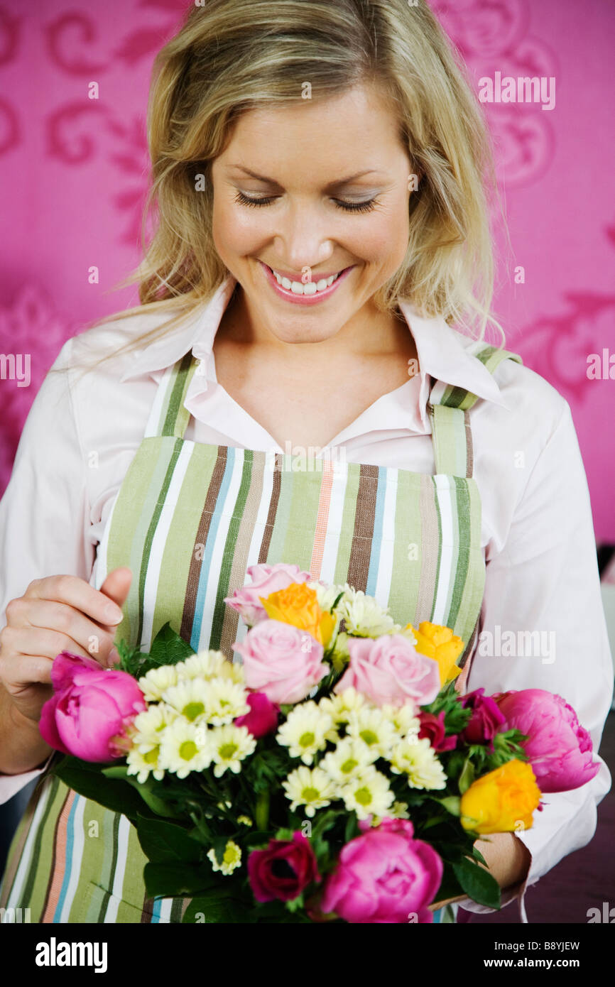 A blond woman working in a flower shop Sweden. - Stock Image