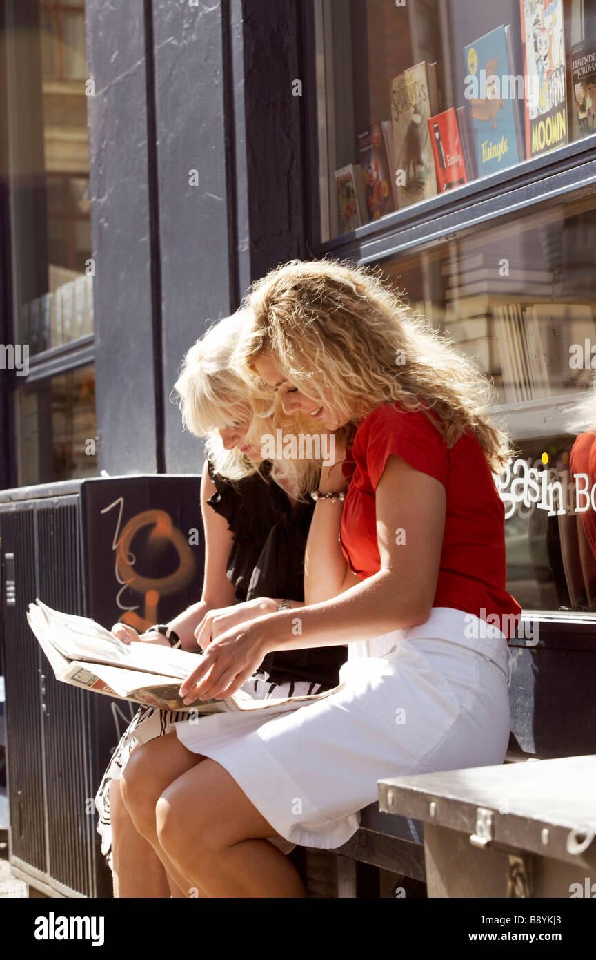 Two friends using a map Copenhagen Denmark. - Stock Image