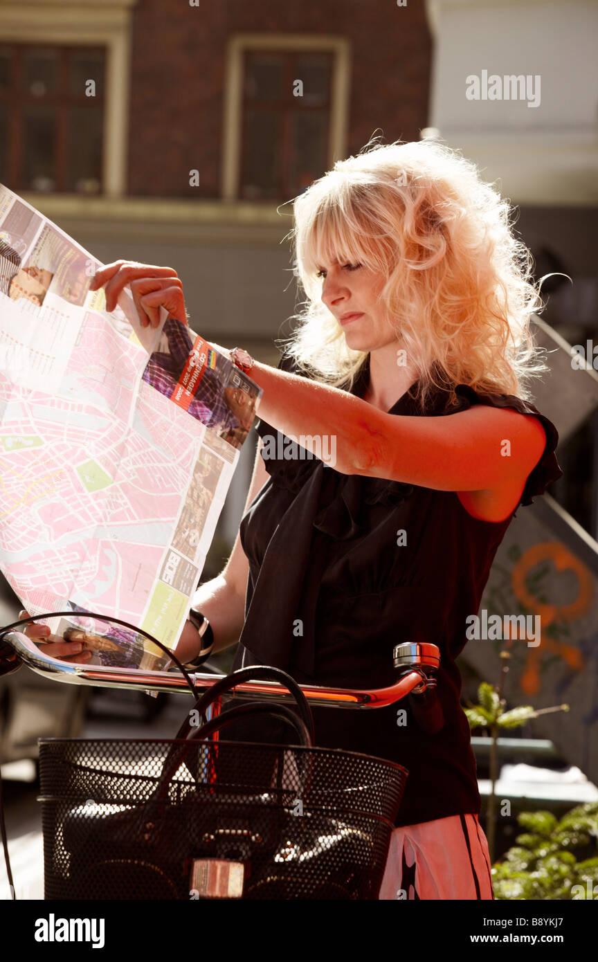 A woman on a bike using a map Copenhagen Denmark. - Stock Image