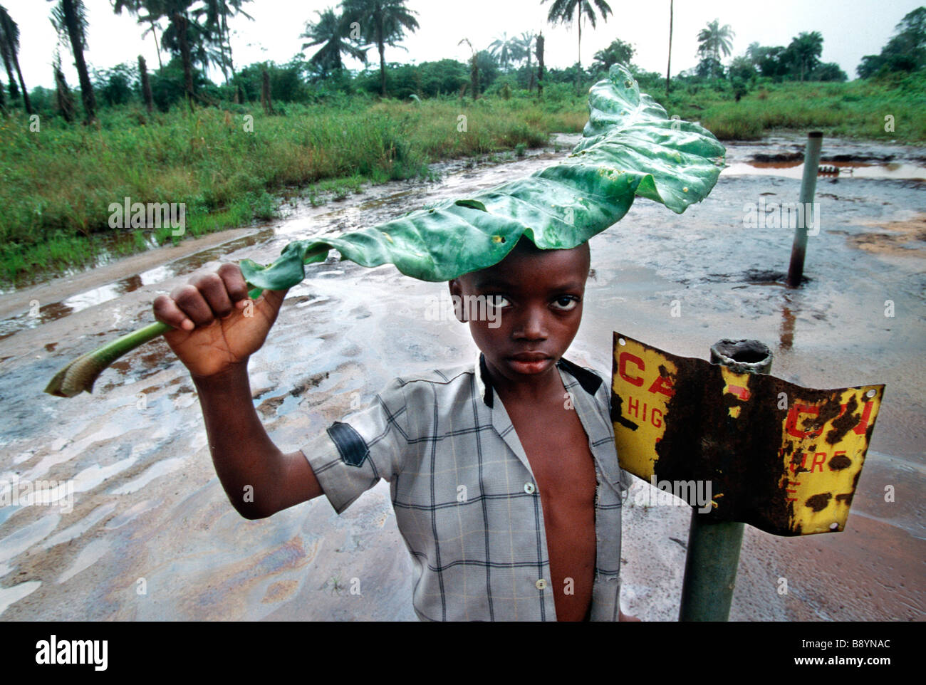 Nigeria: A boy stands besides a danger sign on oil contaminated area in Ogoniland, Nigeria - Stock Image