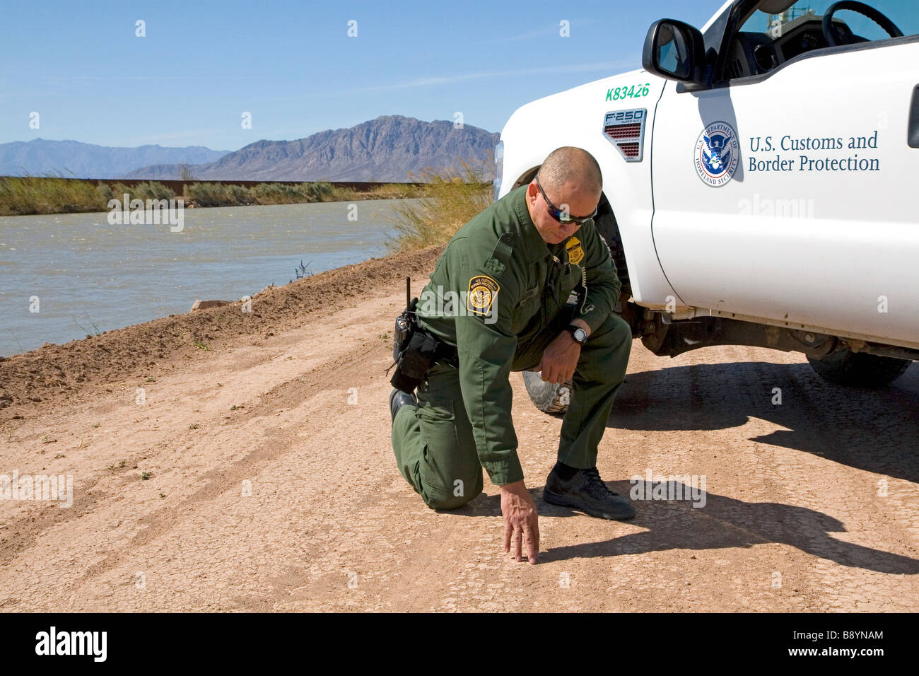 U S Border Patrol agent checking for footprints at the U S Mexico border along the All American Canal near Calexico - Stock Image