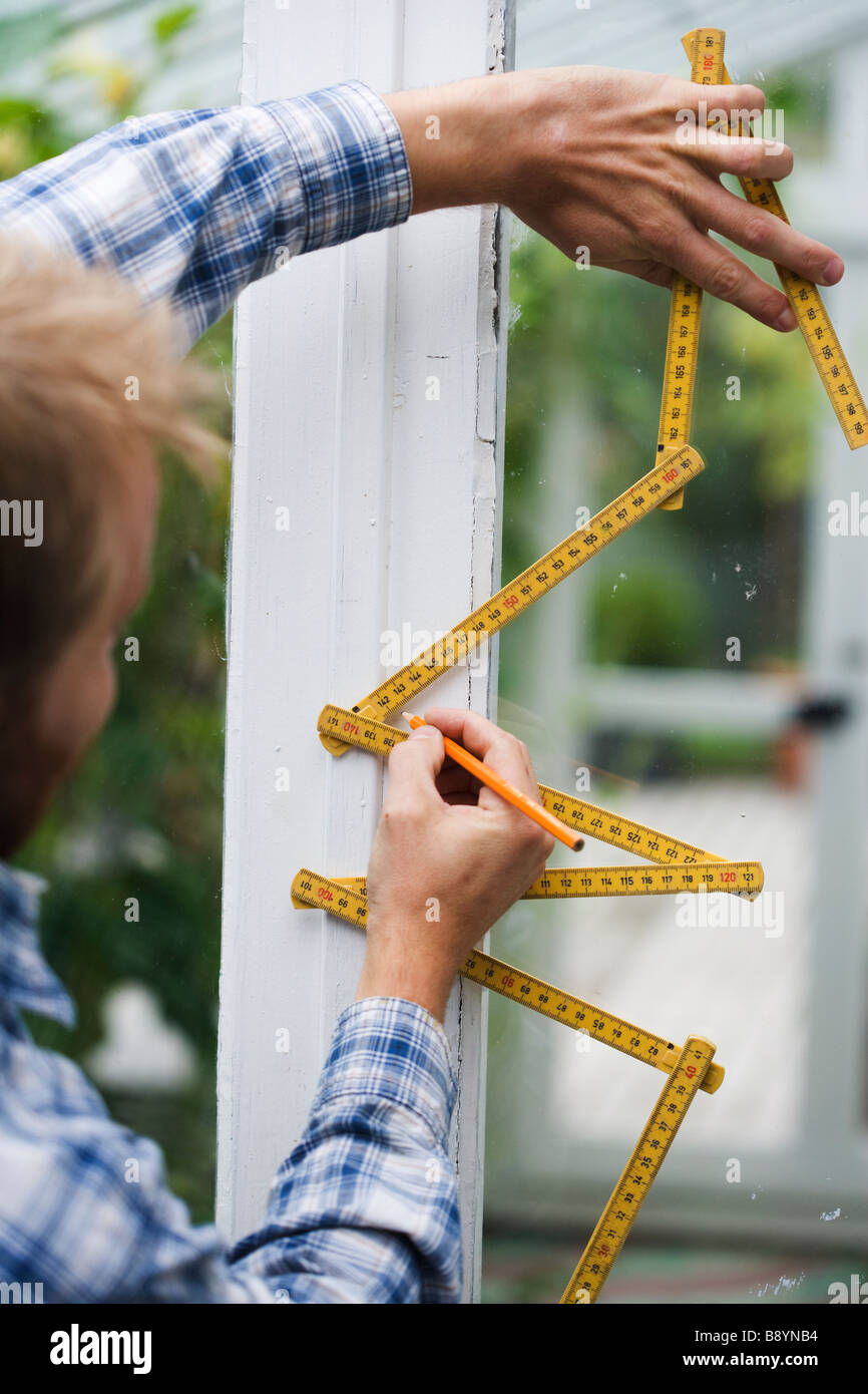 A man using a folding rule Sweden. - Stock Image
