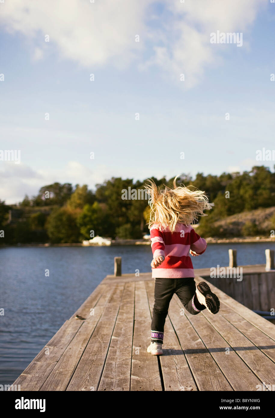 A girl running on a jetty Stockholm archipelago Sweden. - Stock Image