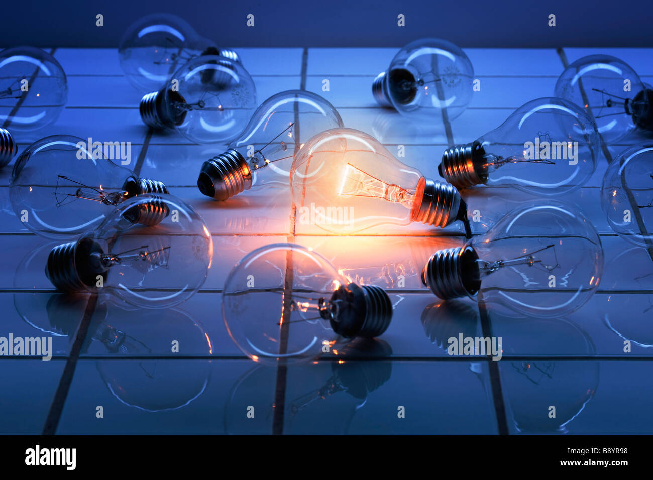 several light bulbs lying on a tiled floor, one of them lucent - Stock Image