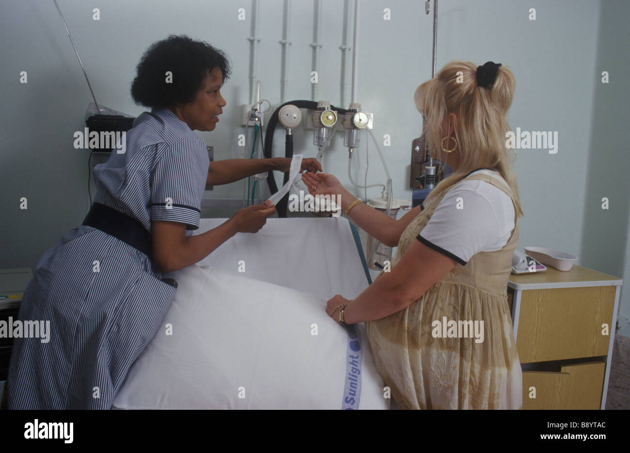 nurse showing pregnant woman around a delivery suite - Stock Image