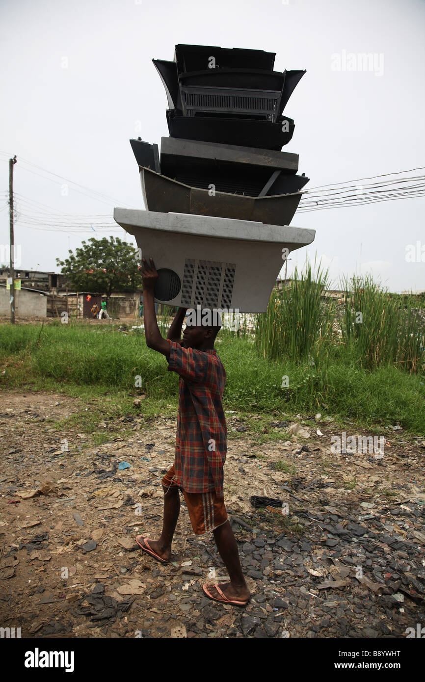 A young boy is carrying a stack of empty TV cases on his head, walking past an electronic dump site in Alaba Int - Stock Image