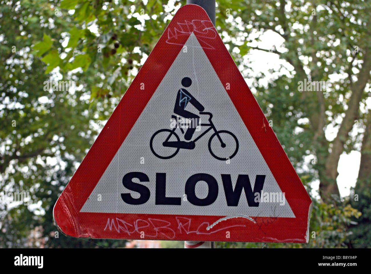 british red and white triangular road sign warning cyclists to go slow Stock Photo