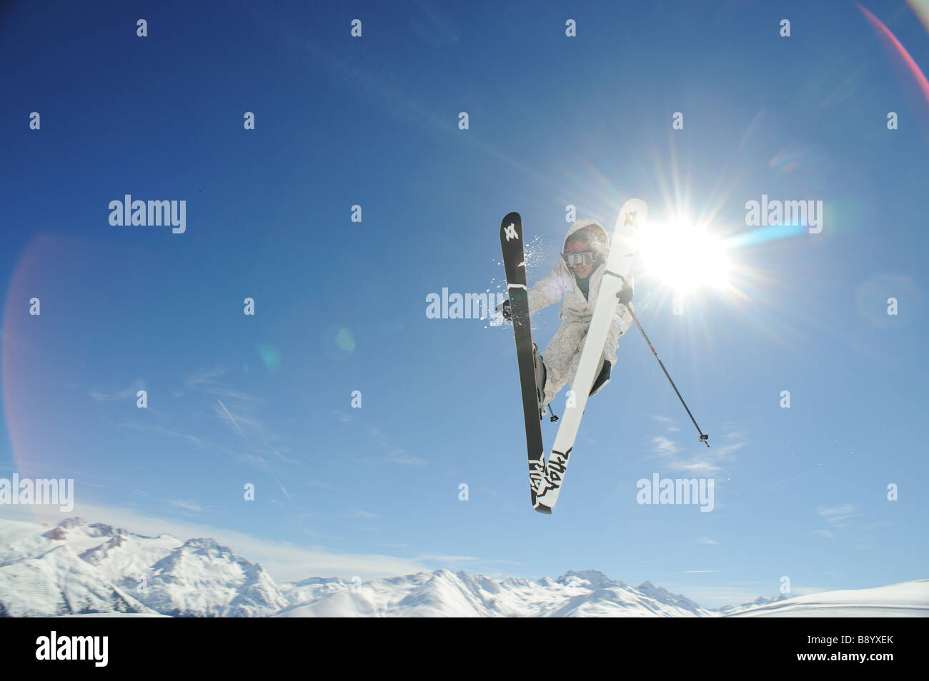 Freeskier performing a jump in the swiss alps - Stock Image