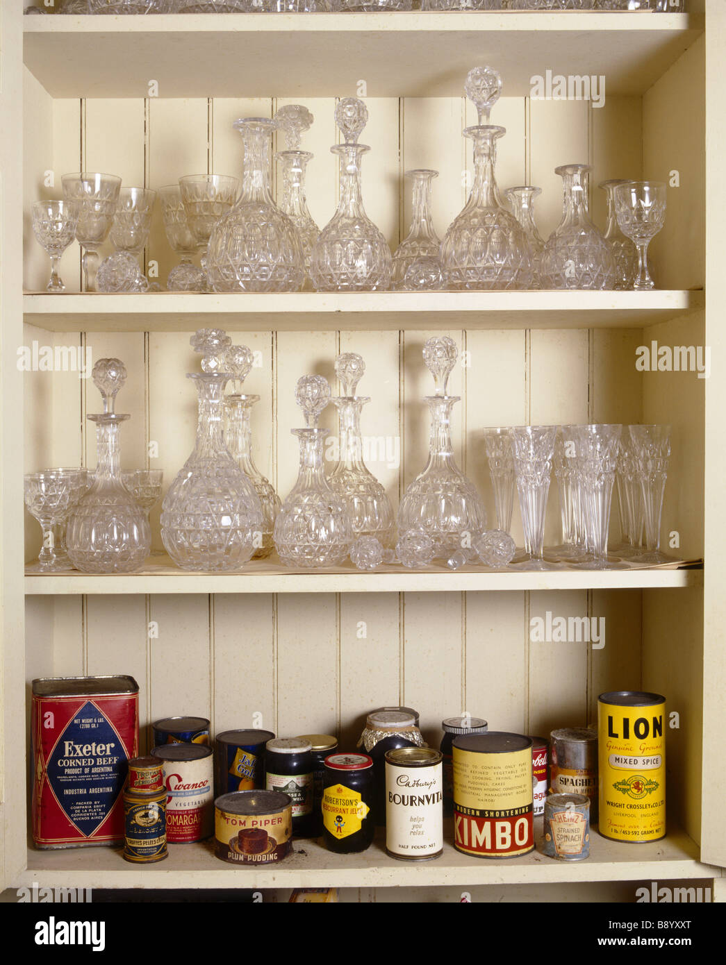 Cut glass decanters on two shelves with tins and groceries on the bottom shelf in a pantry cupboard at Tyntesfield - Stock Image