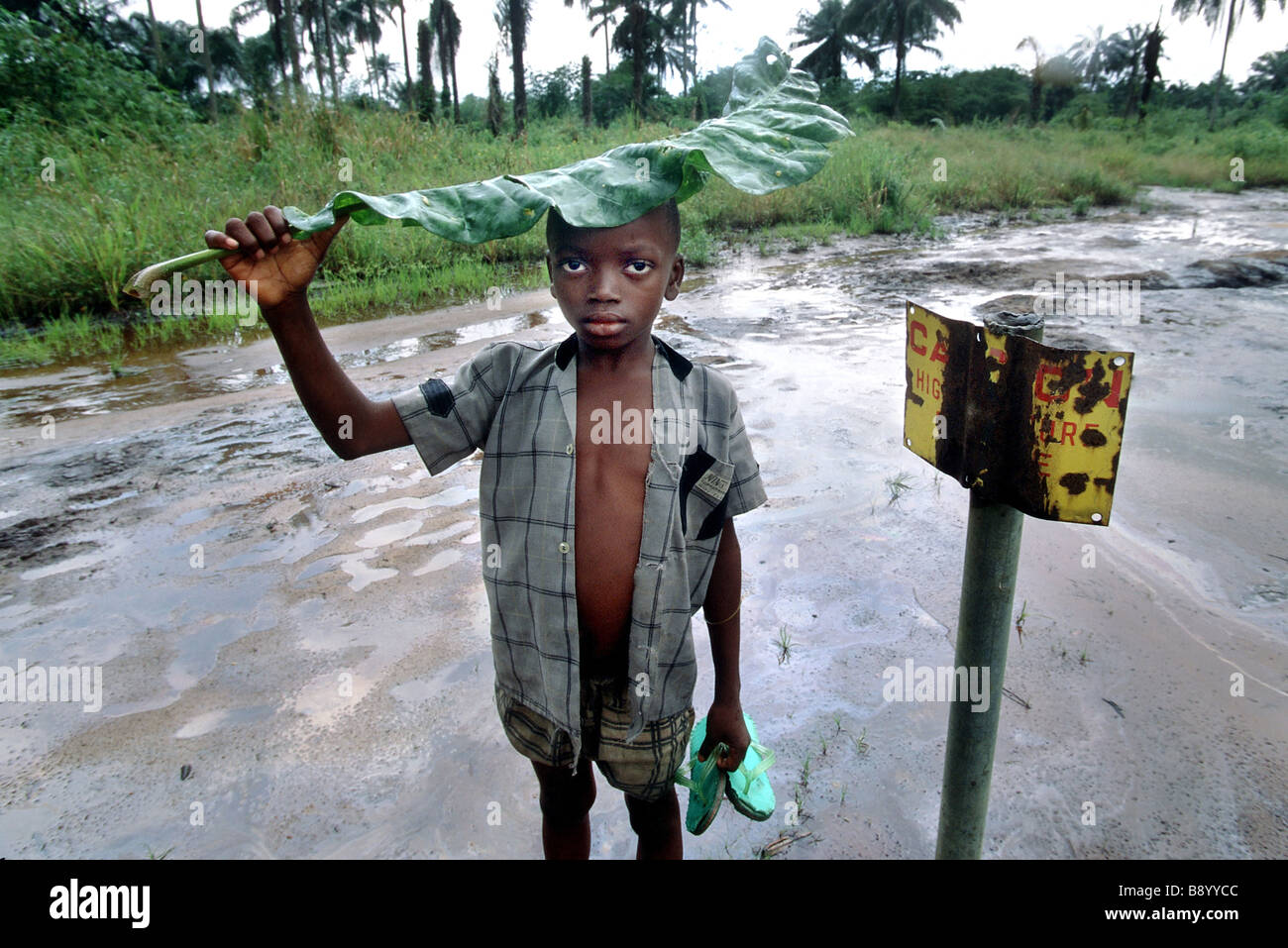Nigeria: A boy stands besides a danger sign by oil contaminated area in Ogoniland - Stock Image