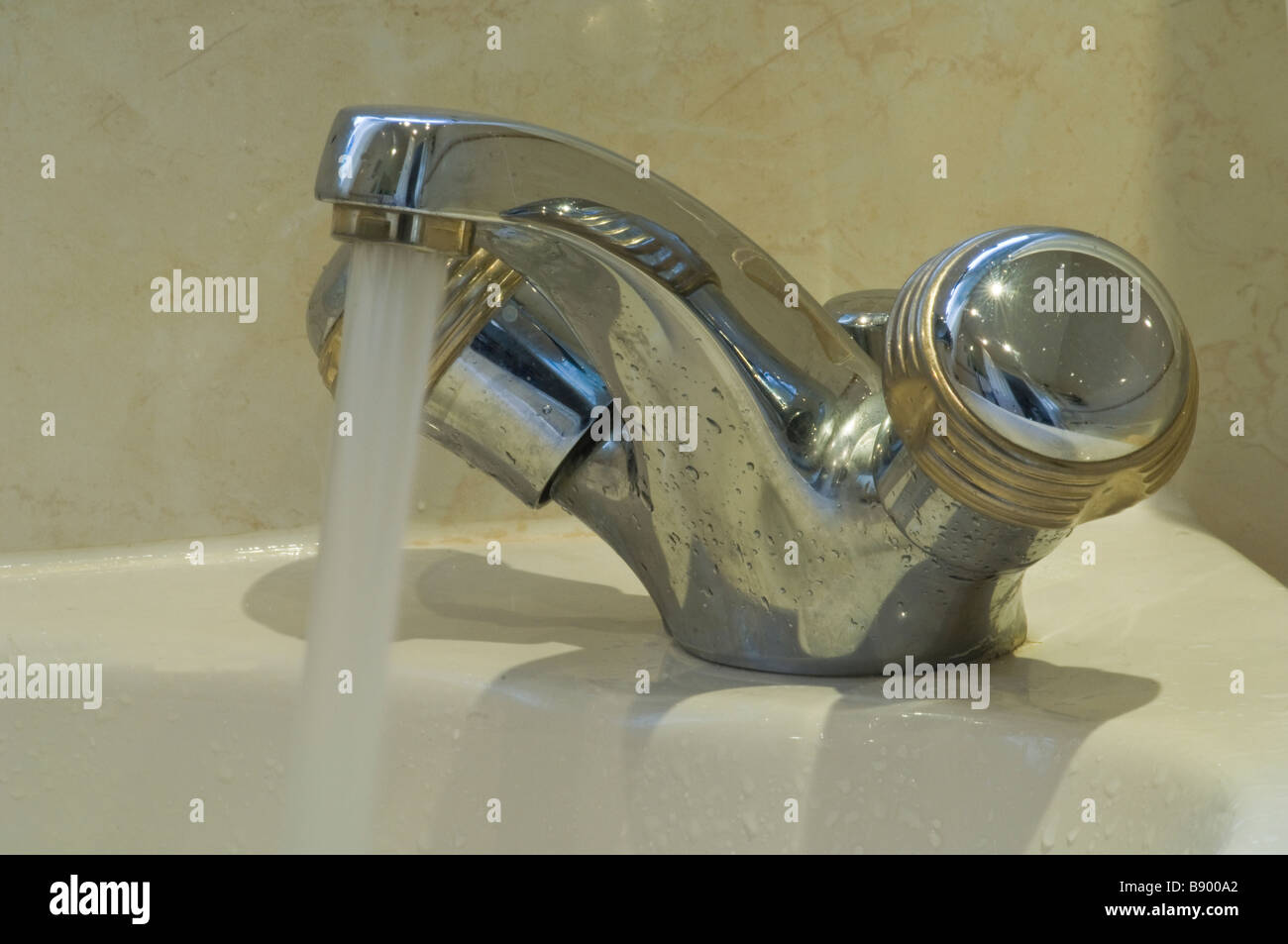 Bathroom tap with the water left running to illustrate wasting water - Stock Image