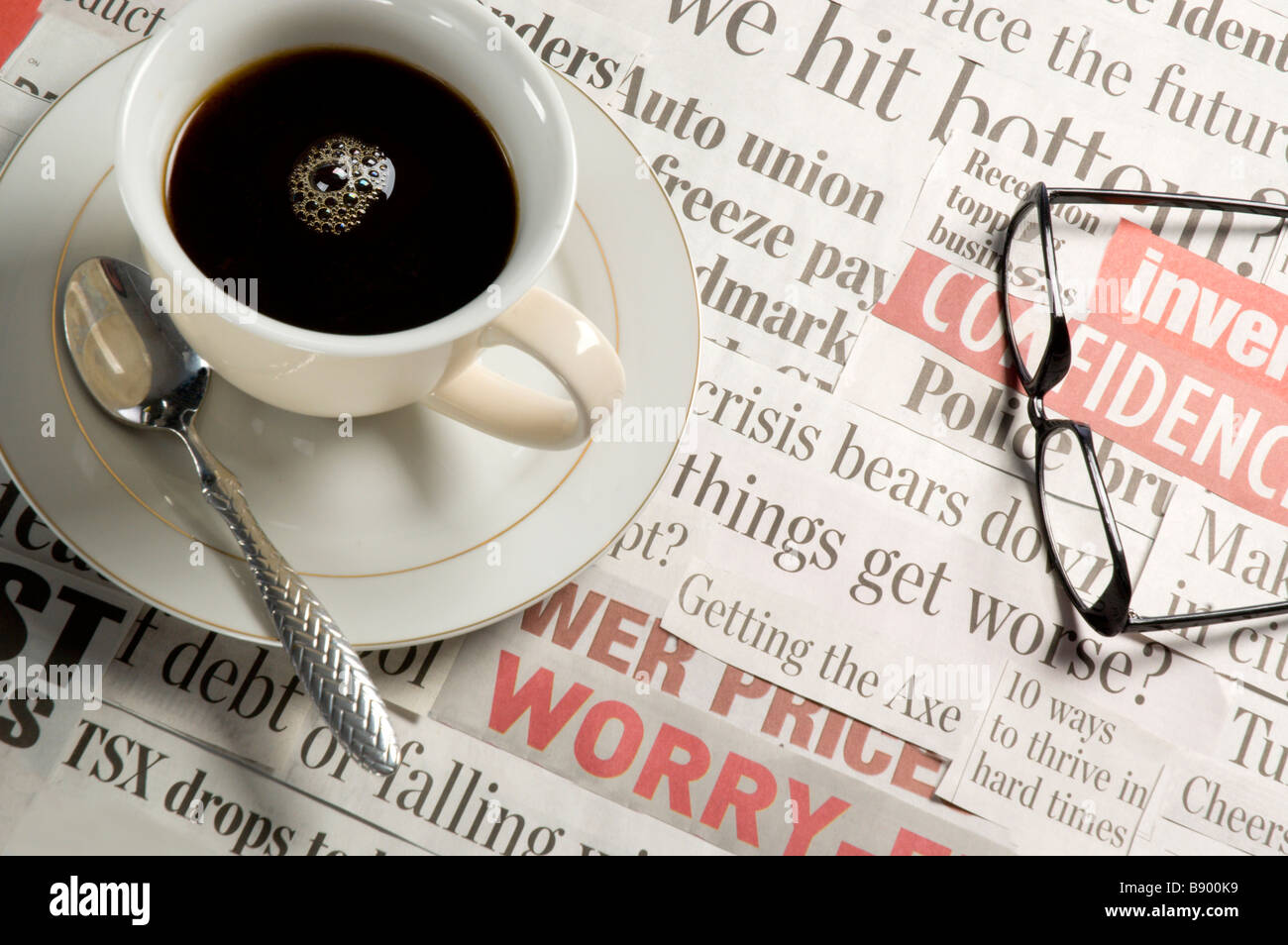 Coffee breakfast over top of bad news headlines in the newspaper - Stock Image