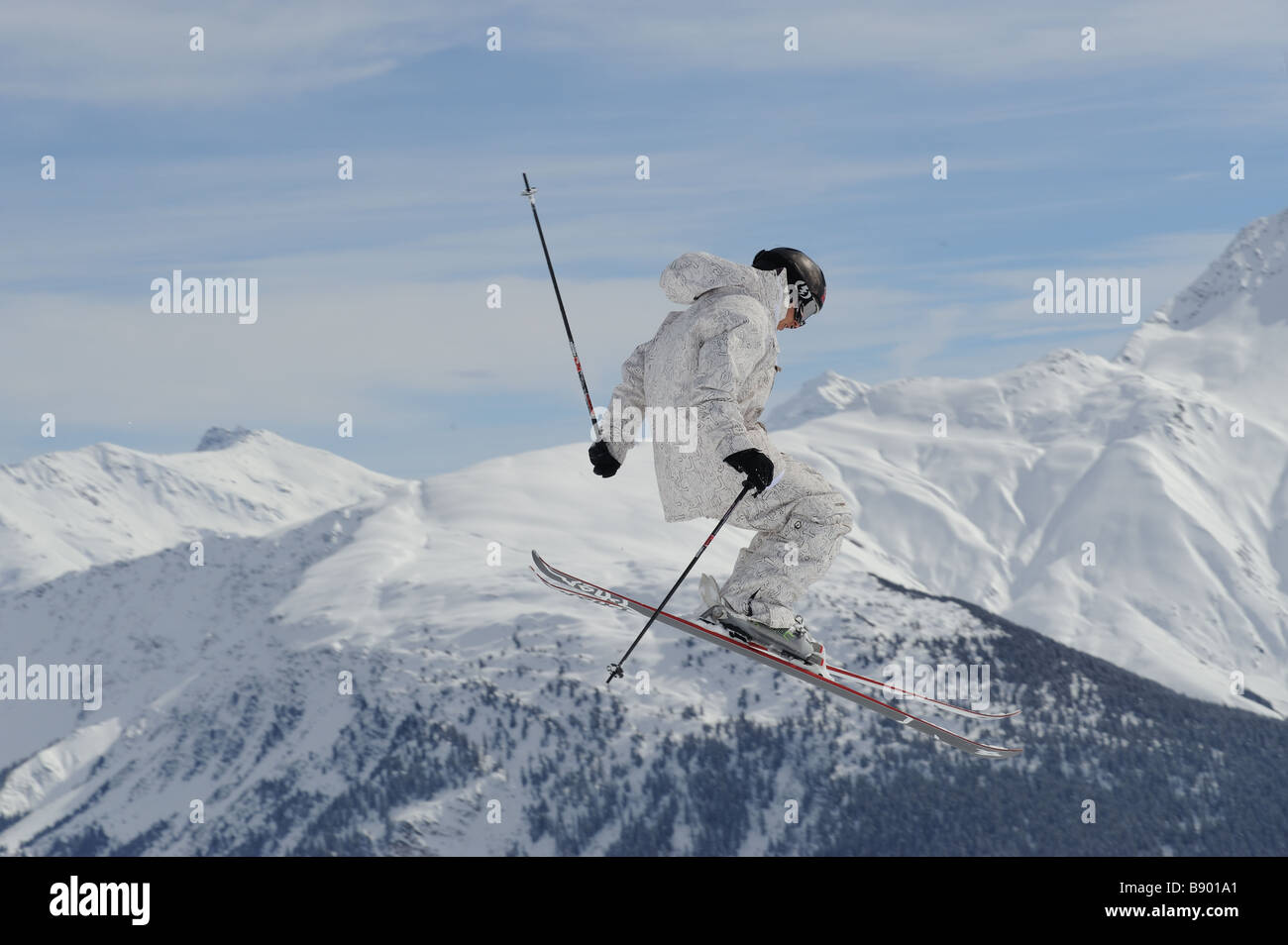Freeskier jumping wildly into the skies in the swiss alps - Stock Image
