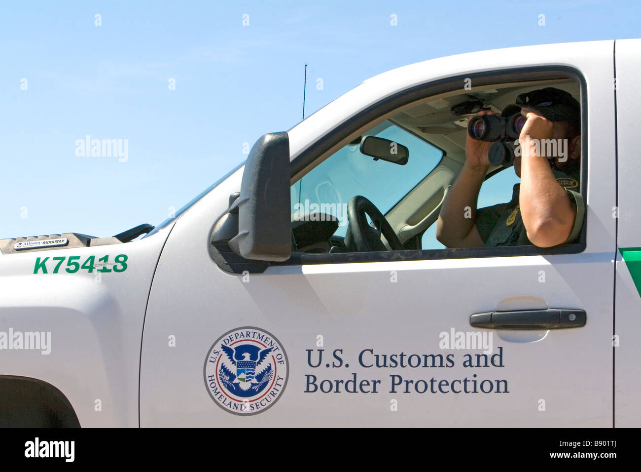 U S Border Patrol agent at the U S Mexico border along the All American Canal near Calexico California - Stock Image