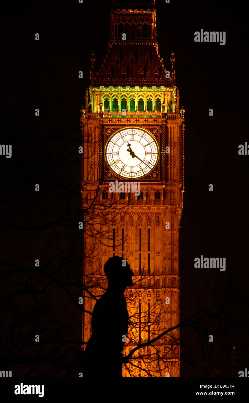 A night time view of Big Ben at the Palace of Westminster London with the Jan Christiaan Smuts statue in silouette. - Stock Image