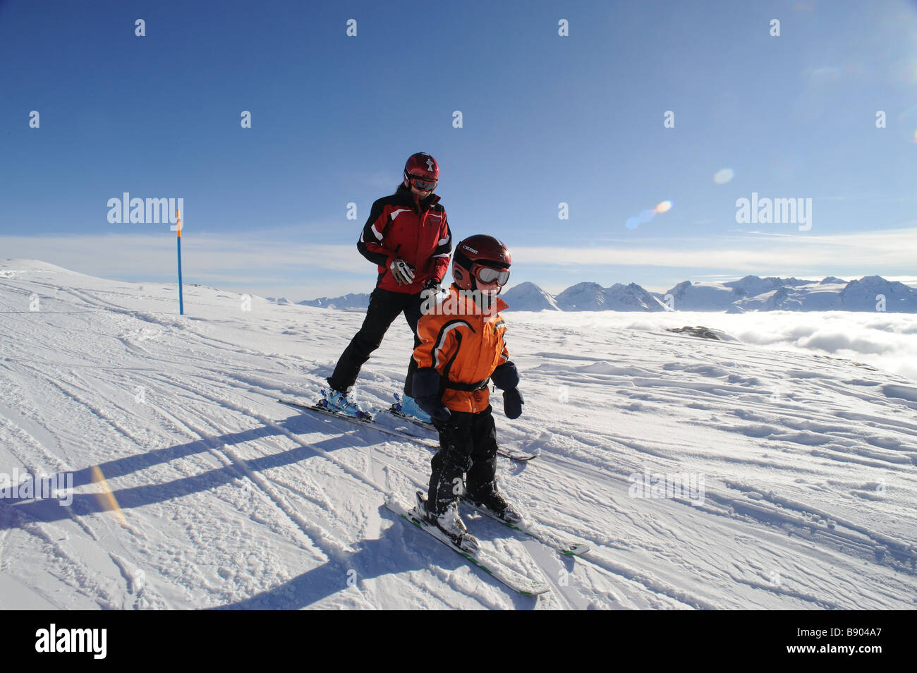 Little boy learning how to ski from his sister - Stock Image