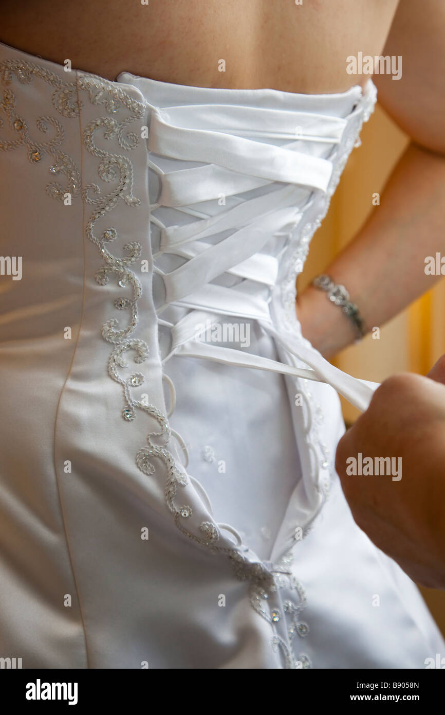Back of white wedding gown, dress with embossed detail, plaiting and ornate decoration - Stock Image