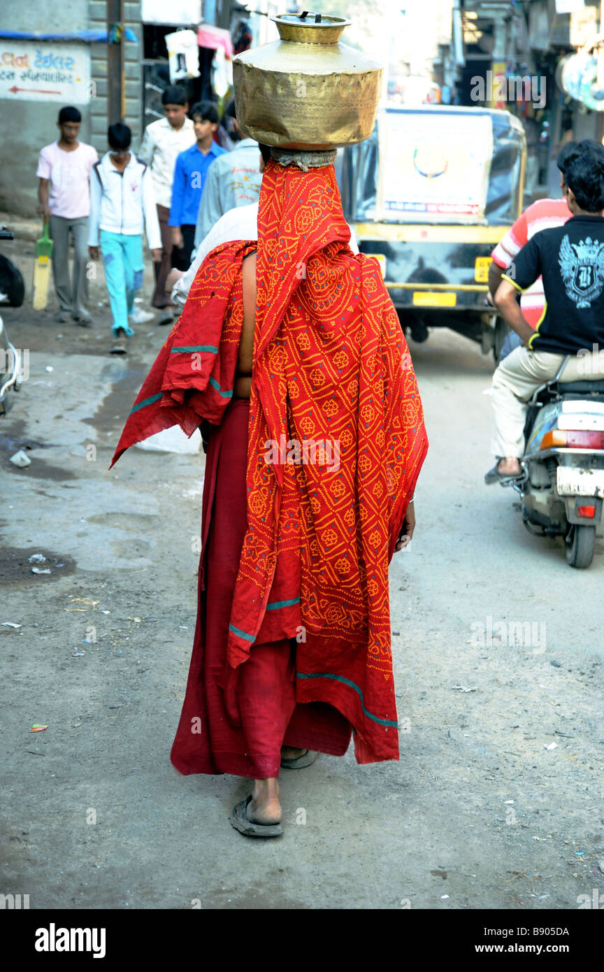 Indian woman brightly dressed carrying water jug on her head - Stock Image