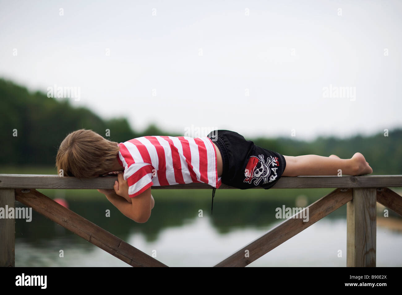 A boy lying on a fence Sweden. - Stock Image