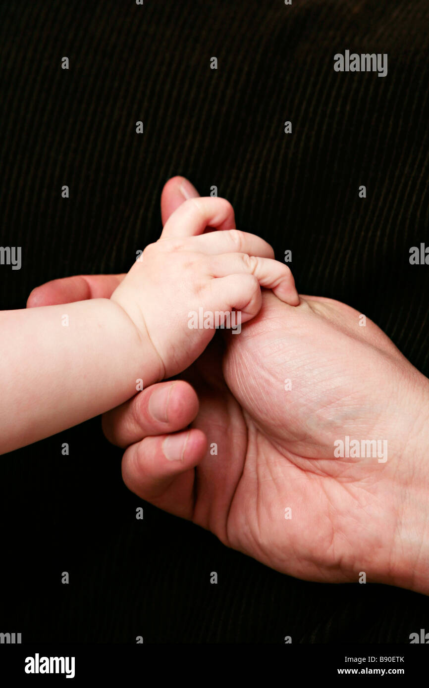 An adult hand and baby hand close-up. - Stock Image