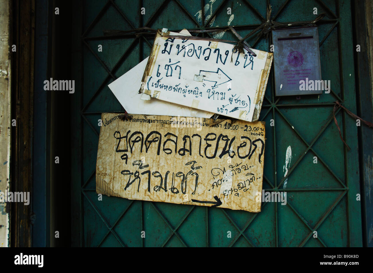 Sticky notes on old door reading in Thai 'Room for rent' - Stock Image