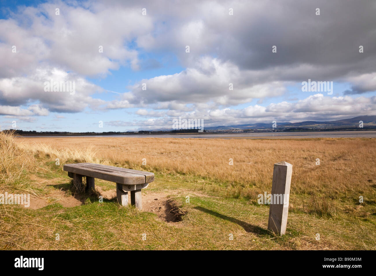 Bench and path waymarker on coastal dunes in National Nature Reserve on Menai Strait. Newborough Warren Anglesey - Stock Image