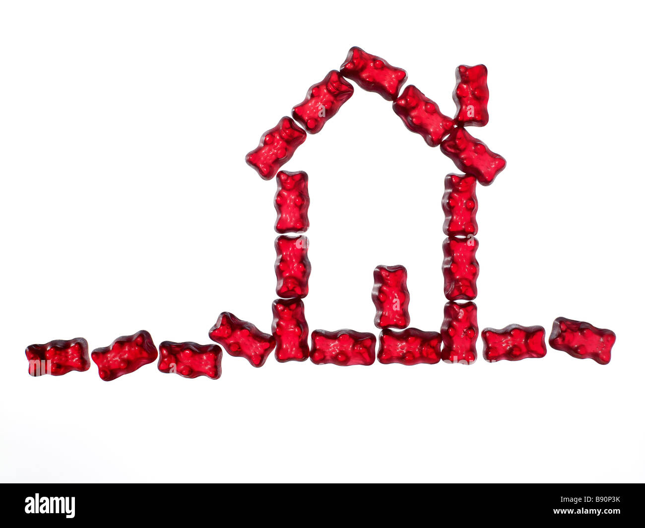 red jellybabies formed as a house on white background - Stock Image