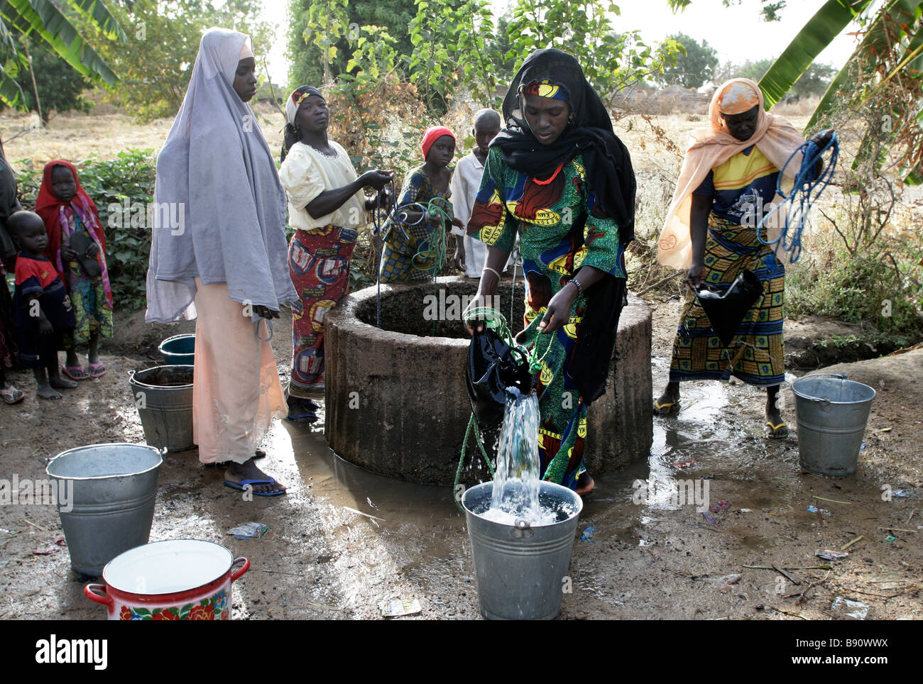 Nigeria: woman drawing fresh water from a well - Stock Image