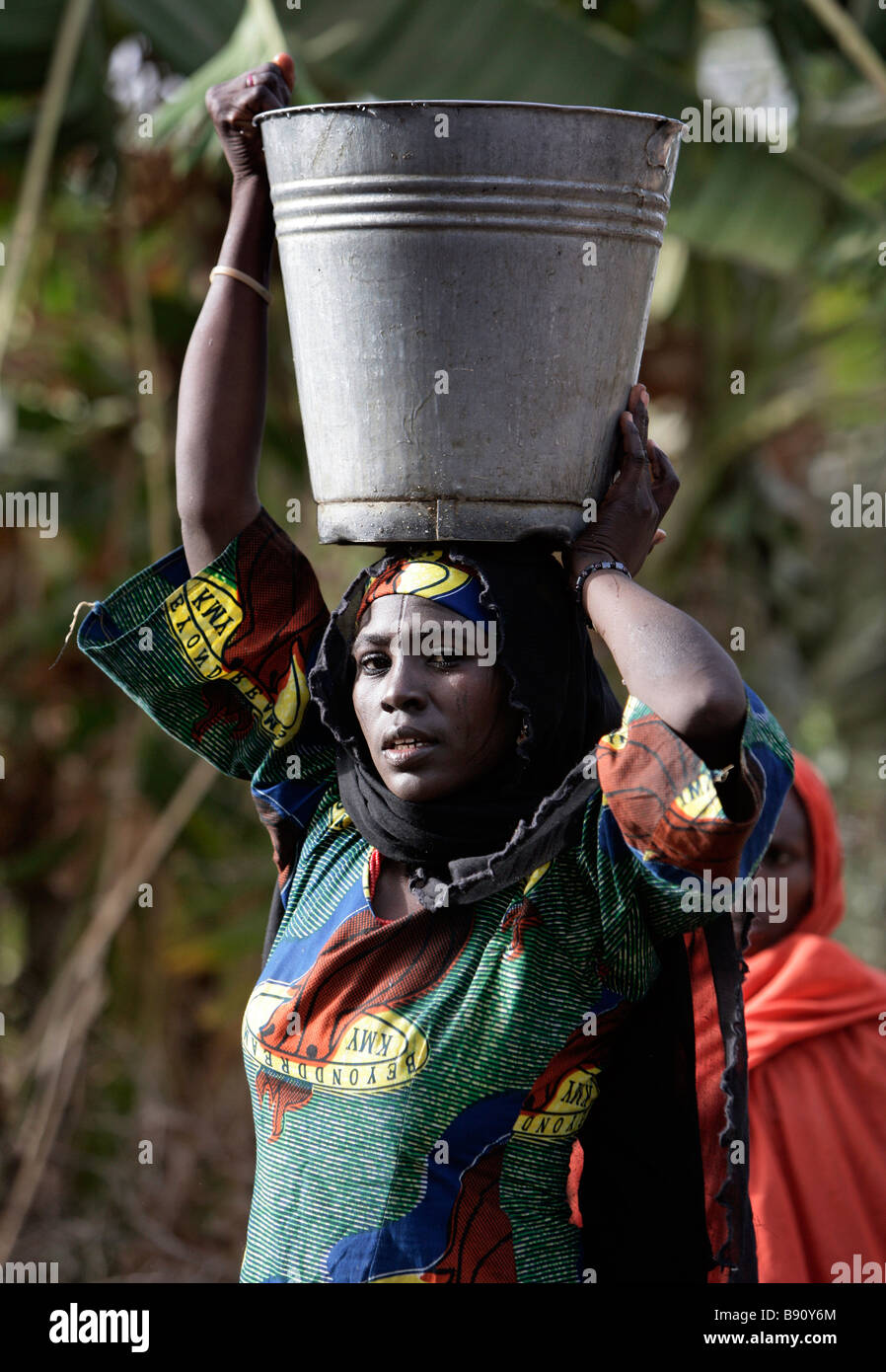 Nigeria: Woman with a water bucket balanced on her head - Stock Image