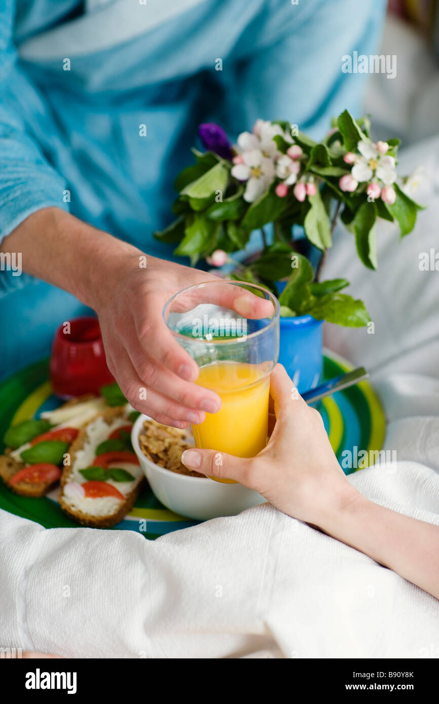 A young couple having breakfast in bed. - Stock Image