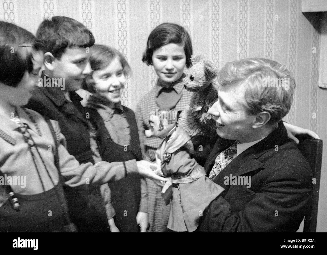 Artist Sergei Obraztsov right showing his dolls to young visitors - Stock Image