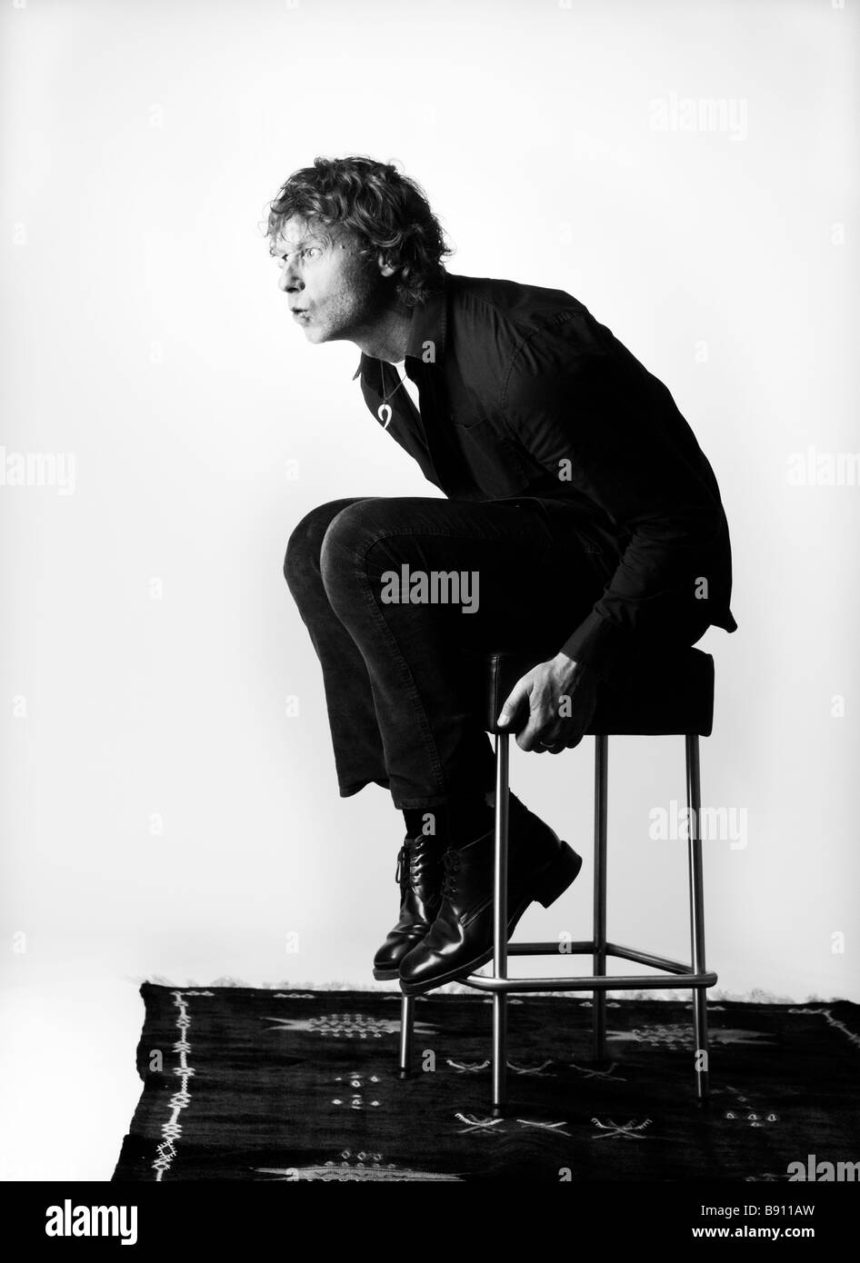 A man sitting on a stool. - Stock Image