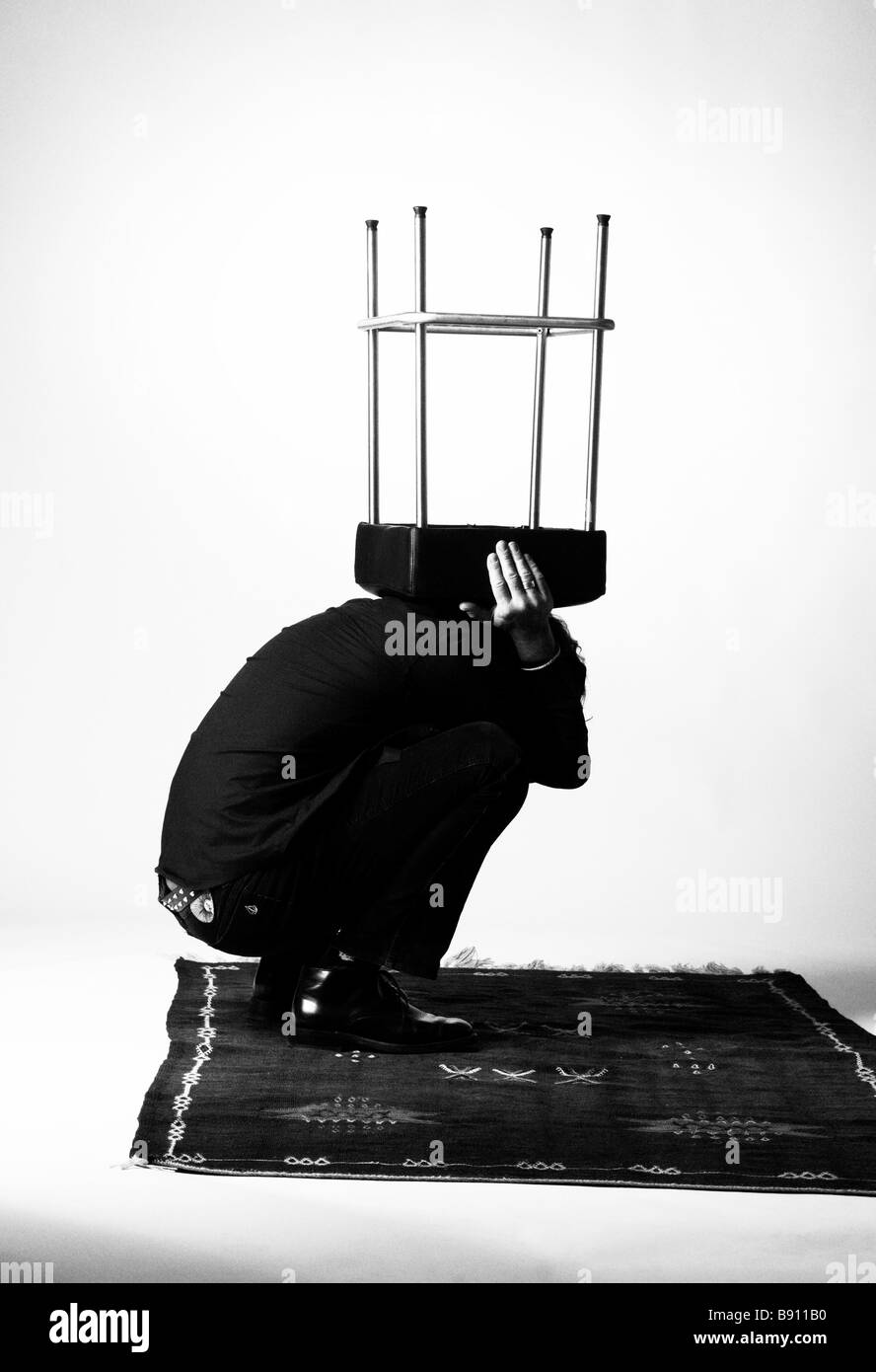 A man with a stool on his head. - Stock Image