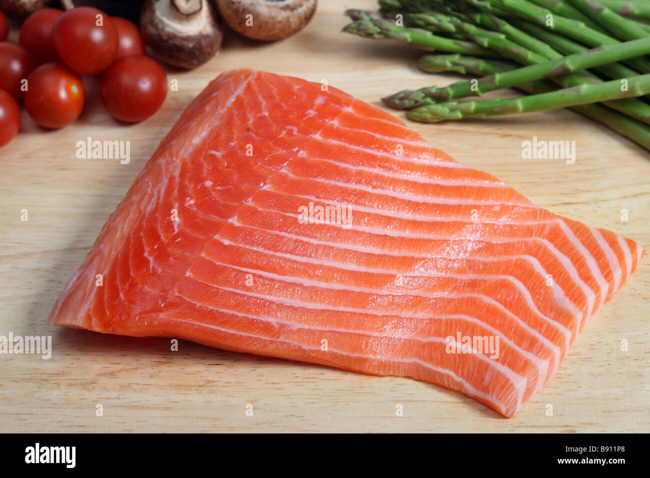 A raw salmon steak on a chopping board with mushrooms asparagus cherry tomatoes and potatoes Stock Photo