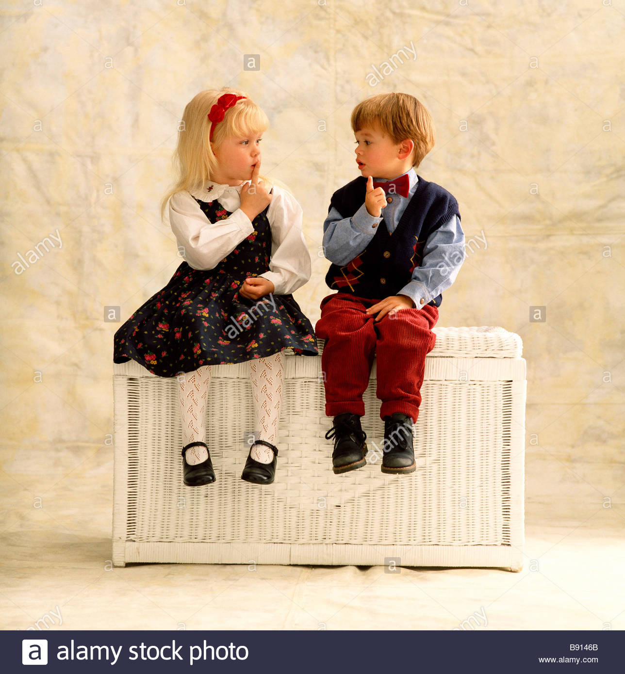 small boy and girl sitting together on a hamper stock photo