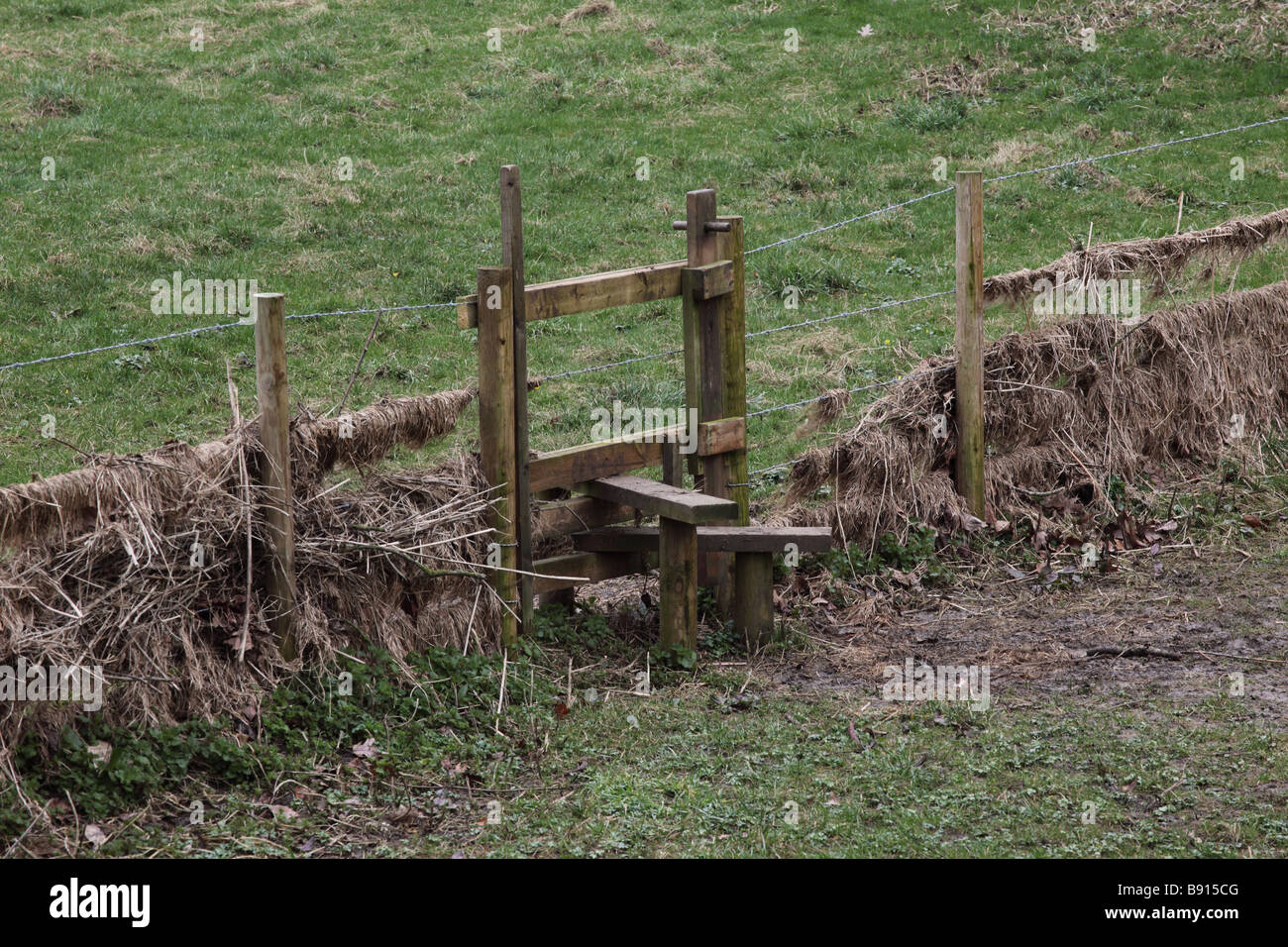 A wooden stile in a barbed wire fence giving access from one field to another - Stock Image
