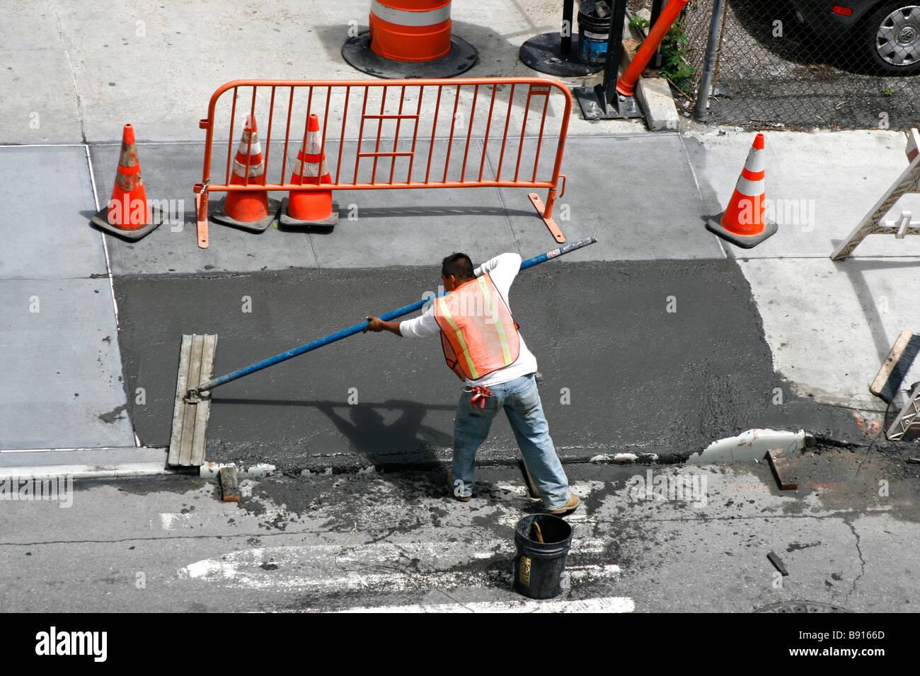 Man smoothing a freshly poured wet concrete sidewalk. Stock Photo
