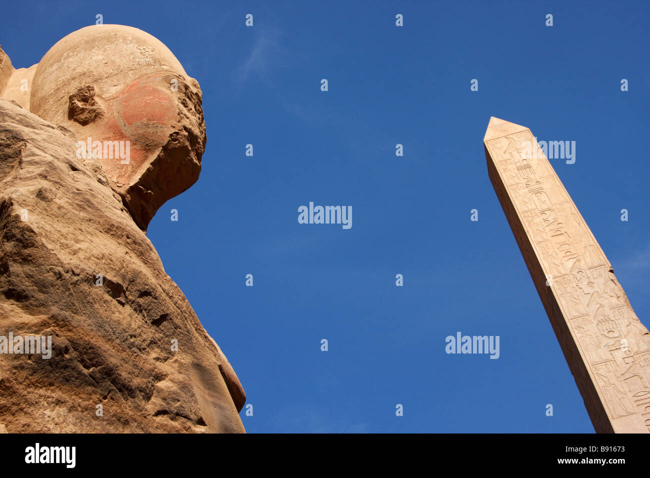 Head of colossal stone carved osiris statue and Obelisk of Queen Hatshepsut against blue sky, Temple of Karnak, Stock Photo