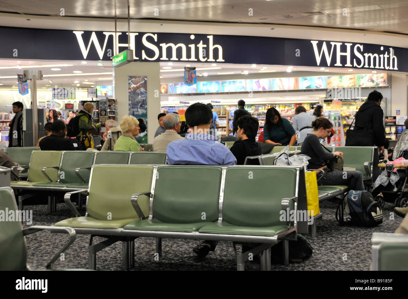 London Heathrow Airport terminal 3 interior passengers in departure lounge beside WH Smith shop Stock Photo