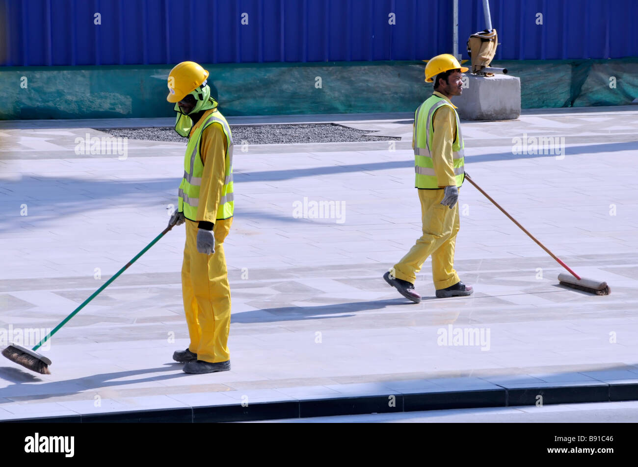 Dubai workmen sweeping up completed part of a construction project - Stock Image