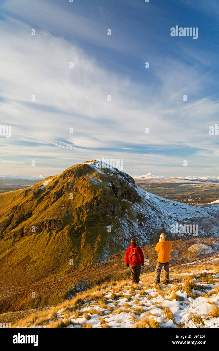 Two walkers admiring Dumgoyne in the Campsie Fells near Glasgow from neighbouring Dumfoyn Ben Lomond is in the background - Stock Image