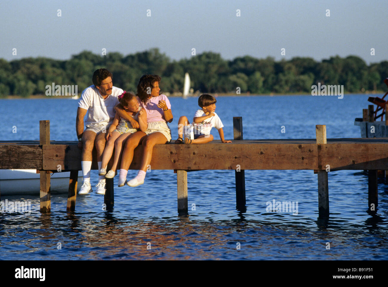 FAMILY SITS ON DOCK ON LAKE HARRIET, A POPULAR INNER-CITY LAKE AND PARK AREA IN MINNEAPOLIS, MINNESOTA.  SUMMER. - Stock Image